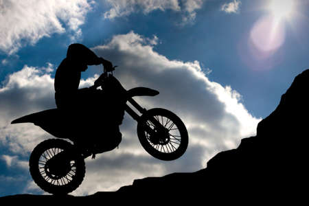 Motocross - silhouette with a rock and blue sky with sun photo