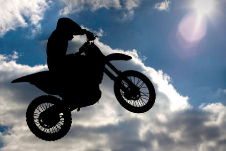 Motocross - silhouette with blue sky with sun photo