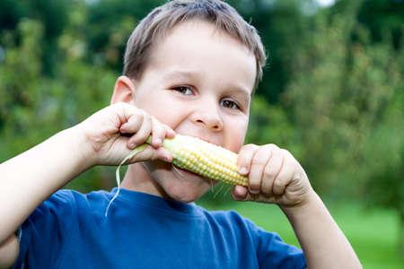 elote: muchacho que come maíz joven al aire libre Foto de archivo