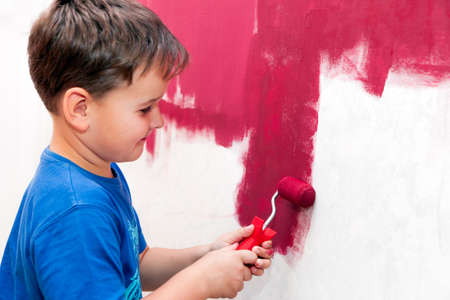 the red wall: boy painting the wall red in the apartment