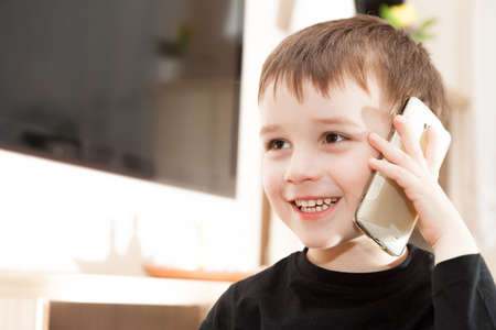 Cute little baby boy is talking on cell phone Foto de archivo