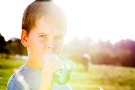 respire: Boy using inhaler for asthma in village with summer sunset Stock Photo
