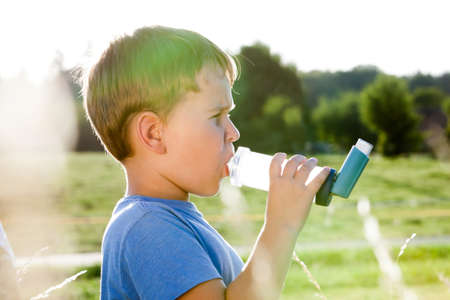 Boy using inhaler for asthma in village with summer sunset Stock Photo