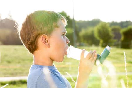 inhaler: Boy using inhaler for asthma in village with summer sunset Stock Photo