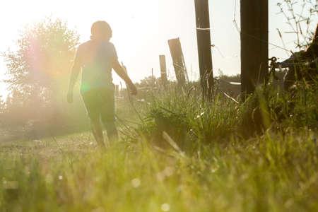 caminando: solo un niño caminando por un camino de tierra a la puesta del sol a lo largo de la valla de madera
