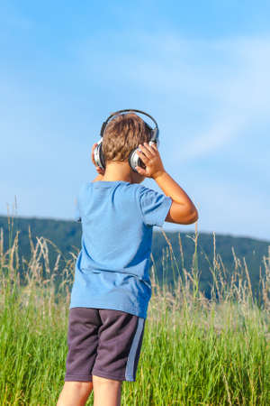6 year old: Cute 6 year old boy listening to music on headphones in nature