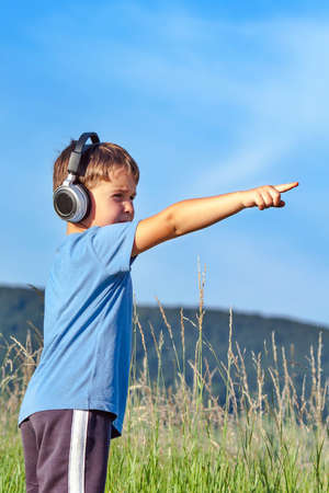 sensations: Cute 6 year old boy listening to music on headphones in nature