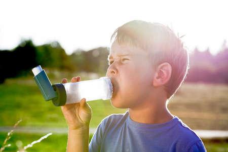 asma: Muchacho que usa el inhalador para el asma en la aldea con la puesta del sol del verano