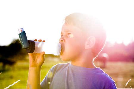 asthma: Muchacho que usa el inhalador para el asma en la aldea con la puesta del sol del verano