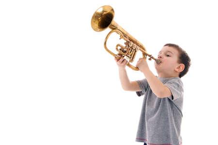 jonge jongen blazen in een trompet tegen de witte achtergrond