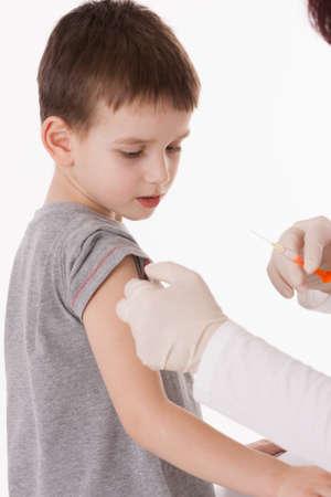 inyeccion: Doctor que da una inyección en el brazo del niño en aislado. Foto de archivo