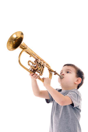 young boy blowing into a trumpet against white background Stock Photo