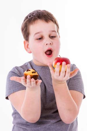 magdalenas: niño pequeño con el alimento aislado en el fondo blanco - manzana o un muffin