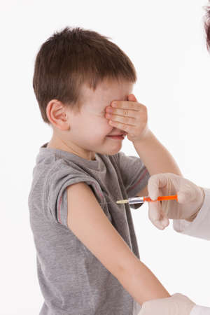 Doctor giving a child injection in arm on isolated image. Stock Photo