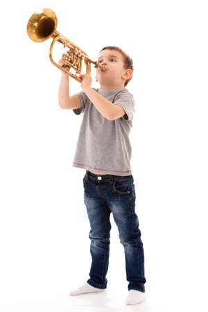 young boy blowing into a trumpet against white background Foto de archivo