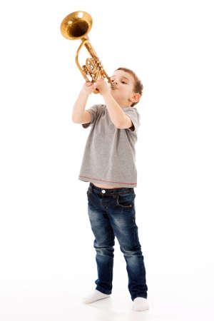 trompeta: muchacho joven que sopla en una trompeta contra el fondo blanco Foto de archivo