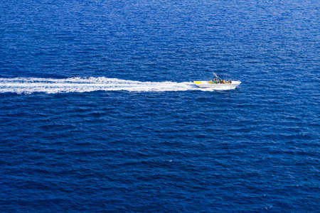 motorboat: Kolymbia beach with the rocky coast in Greece. Motorboat and speed  in blue sea. Stock Photo