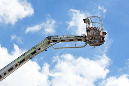 Fire truck ladder leading up into blue sky. Stock Photo