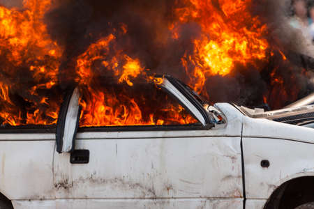 burning and then extinguish an old white car - Exercise firefighters Stock Photo