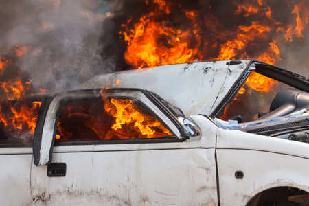 extinguish: burning and then extinguish an old white car - Exercise firefighters Stock Photo