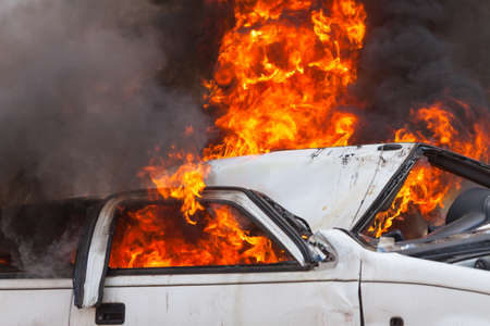 burning and then extinguish an old white car - Exercise firefighters 스톡 콘텐츠