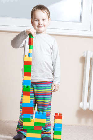 standing and smiling boy with built stack of colored cubes Stock Photo