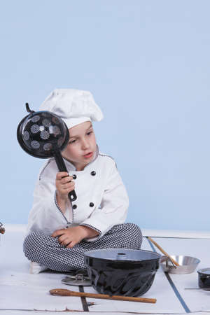 One little boy as chef cook making salad, cooking with vegetables. Isolated on white.