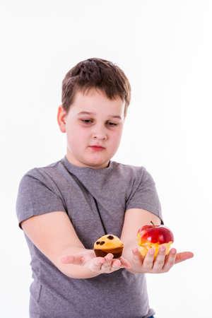 manzana roja: niño pequeño con el alimento aislado en el fondo blanco - manzana o un muffin