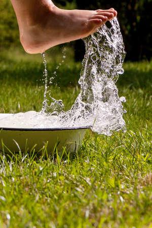 Little boy and splash of water in the summer garden