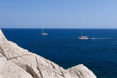 Kolymbia beach with the rocky coast in Greece. Motorboat and speed  in blue sea. Stock Photo