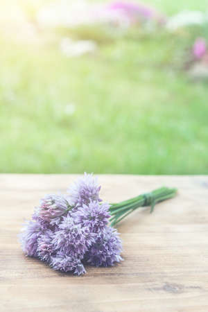 Flower chives tied in a snop on a natural wooden cutting board