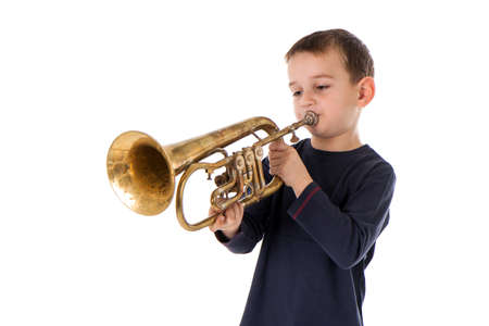 young boy blowing into a trumpet against white background Reklamní fotografie