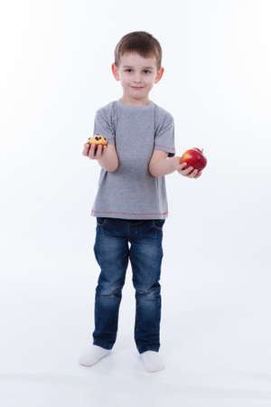 little boy with food isolated on white background - apple or a muffin photo