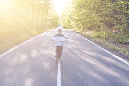 Panning shot of boy walking through a road in the middle of a forest