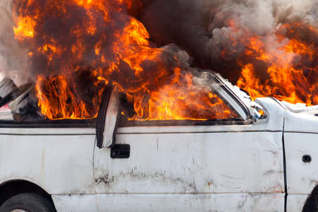 abandon: burning and then extinguish an old white car - Exercise firefighters Stock Photo