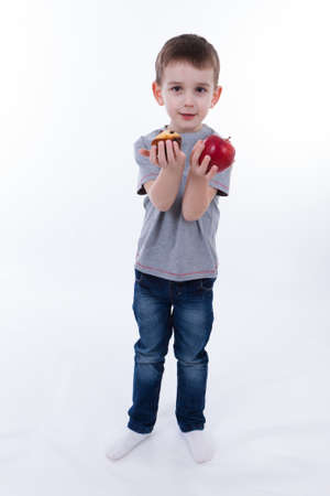 little boy with food isolated on white background - apple or a muffin
