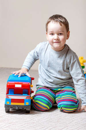 Playing little boy with colored cubes photo