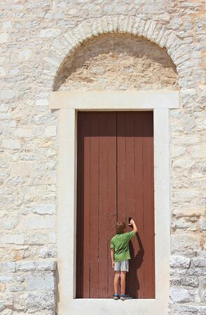 a young curious boy standing before an old door photo