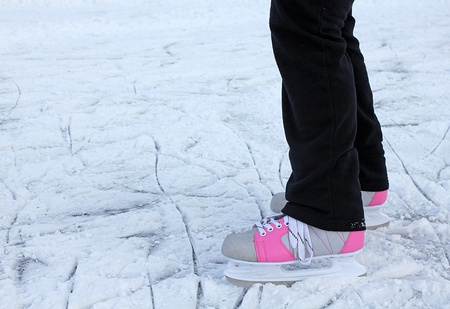 legs of an ice skater on winter ice photo