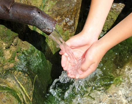 clean hands: fresh water flowing from a spring into a young boys hands Stock Photo