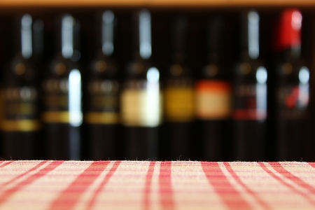 wine bottles on a shelf in the foreground tablecloth shot with limited depth of field photo
