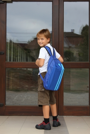 back to school - happy young boy standing in front of the entrance of the school photo
