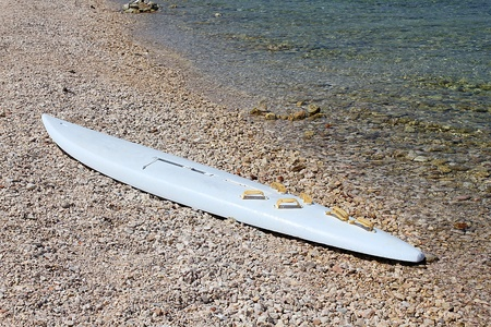 white windsurfing board lying on the beach photo