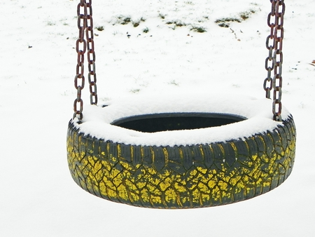 snowy tire swing on the empty playground in winter photo