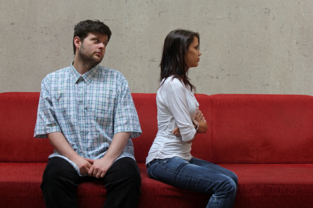 sad couple sitting on a red sofa, young man hopefully watching his girlfriend while waiting for her forgiveness photo