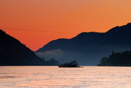 An unpowered car ferry crosses the Danube River at sunrise