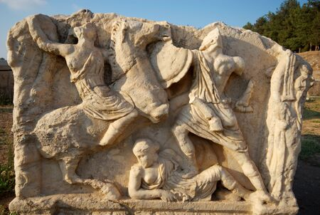 A sarcophagus carving featuring two warriors fighting over a reclining woman, Ephesus, Turkey Stock Photo - 4794819