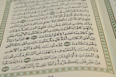 sunni: Open Koran with arabic writing visible