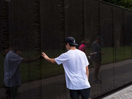 WASHINGTON, USA - AUGUST 25, 2017: A young boy in a white shirt is touching the Vietnam Memorial with his fingers Stock Photo - 117151643