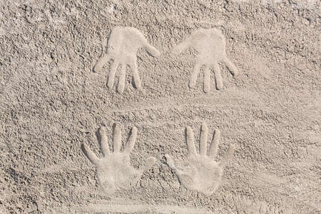 four hands: four hands footprint in the sand at the beach Stock Photo